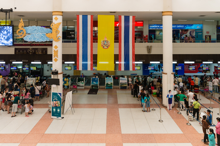 registering: PHUKET, THAILAND - 06 MAY 2014: Registering check-in desks with hanged over big Thai national flag the international departures area at Phuket International Airport.