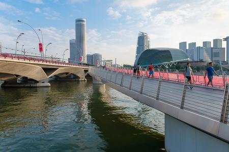 alongside: SINGAPORE - 07 AUG 2015: Tourists strolling along the newly constructed Jubilee Bridge, built for pedestrians alongside the older Esplanade Bridge in Singapore.