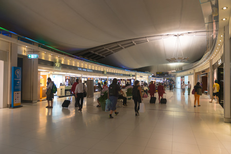 direction sign: BANGKOK, THAILAND - 15 JULY 2014: Passengers walk past a shopping area on their way to the departure gates at one of Suvarnabhumi Airports main terminals.