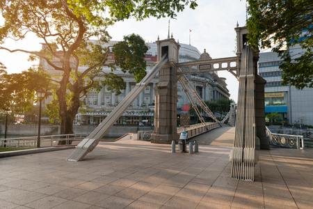 traverse: SINGAPORE - 07 AUG 2015: Historic Cavenagh Bridge, spanning the Singapore River near Raffles Place, with the Fullerton Hotel in the background.