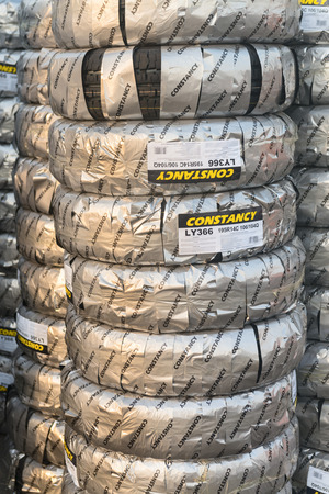 constancy: DUBAI, UAE - 16 JULY 2014: Stacks of new packed car tires produced by Constancy Tyres Co.,ltd in Dubai cargo port