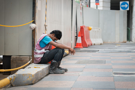 SINGAPORE - 21 DEC 2013: Exhausted construction worker sits on a cement slab at a project worksite in Singapore to take a break. 에디토리얼