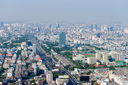 metropolis: Long, straight segment of urban highway cuts through the heart of Bangkok, Thailand, with highrise commercial and residential buildings.