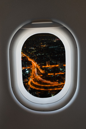 highway interchange: Airplane window from interior of aircraft with view of complex highway interchange at night.