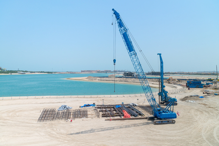 ongoing: Big, blue, mobile, diesel crane, laying out steel framworks and components for an ongoing, beachside construction project. Stock Photo
