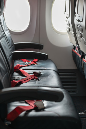 restraints: Standard, coach passenger seats on a commercial airliner, with red seatbelt straps crossed and waiting for use. Stock Photo