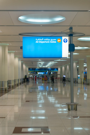 concourse: Lighted informational sign, posted prominently in the center of a main concourse at Dubai International Airport, directs passengers to departure gates.
