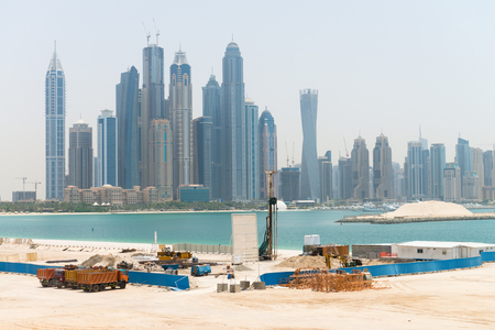 dumptruck: Heavy construction equipment stands by at a waterfront development site near a major metropolitan city, with tall, urban, highrise buildings in the background.