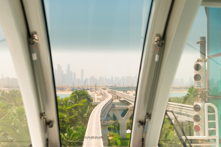 monorail: Looking through the front window of a commuter train to see a monorail track approaching a major urban center in the background.