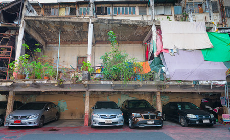 bangkok: BANGKOK, THAILAND - 8 FEB 2016: Cars Parked beneath an Old, but Unfinished Building in Bangkok Editorial