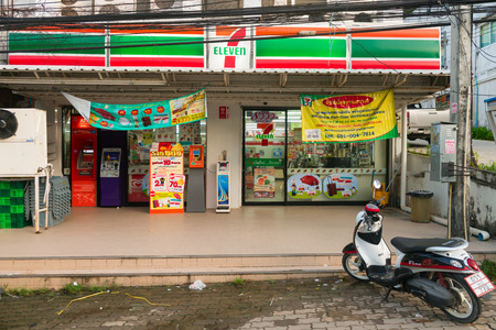 eleven: KRABI, THAILAND - 13 OCT 2014: Seven eleven 711 24hr round-the-clock convenience store in Krabi with atm machines, signs and scooter