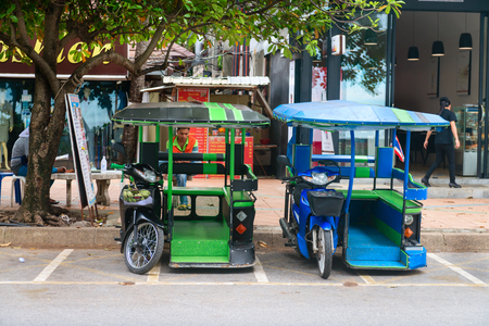a two wheeled vehicle: KRABI, THAILAND - 13 OCT 2014: Green and blue tuk tuk used as tourist taxis parked under a tree in the public street at Ao Nang Krabi, Thailand