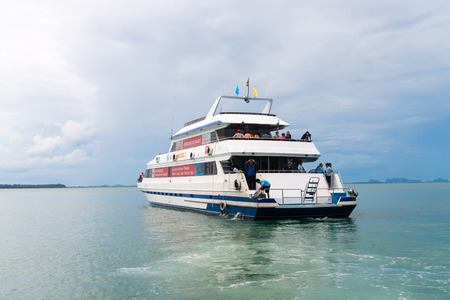 the mainland: KRABI, THAILAND - 12 OCT 2014: Big luxury tourist charter boat ferry with tourists onboard off the mainland from Krabi to Phuket, Thailand.