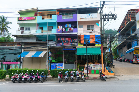 bike parking: AO NANG, KRABI, THAILAND - 14 OCT 2014: Old  chaotic colorfull apartment block with motor bike parking in front of the building.