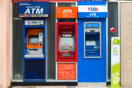withdrawal: AO NANG, KRABI, THAILAND - 14 OCT 2014: Row of ATM cash point machines in different colors with screens for banking and withdrawal of cash