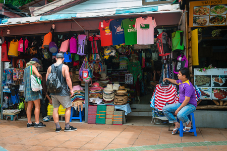 shop keeper: AO NANG, KRABI, THAILAND - 15 OCT 2014: Retail market stall selling souvenirs, hats, colorful balls and bags outside and the shop keeper sitting on a stool.