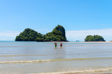 thai stretch: KRABI, THAILAND - 13 OCT 2014: Tourists couple walking in shallow water with tropical islands and sand beach in the background and clear blue sky at Ao Nang