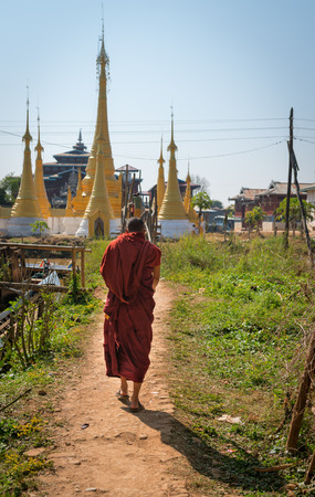 dirt path: Burmese, Buddhist monk walks along a dirt path toward the gold painted stupas of a temple in Myanmar.
