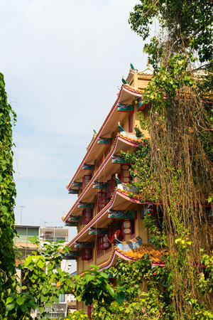 tiered: Vines and greenery hang around the beautiful, multi tiered exterior of a traditional, Chinese, Buddhist temple in Bangkok, Thailand.