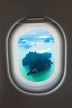 wispy: Aerial view of wispy clouds over tiny, rocky, tropical islands, taken from the passenger window of a commercial airliner.