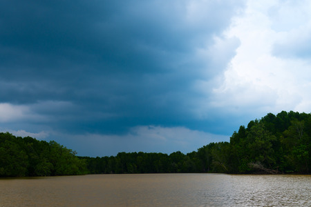 threaten: Ominous clouds threaten to drop heavy rains over the dense vegetation and silty waters of a tropical estuary in Southeast Asia. Stock Photo