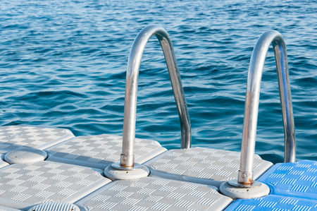 hand rails: Stainless steel hand rails of a swimmers boarding ladder, mounted on the edge of a plastic, floating dock in a tropical sea.