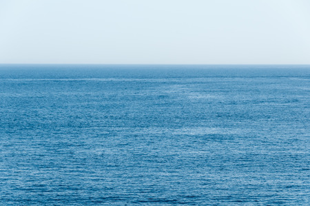 Flat, warm waters of a tropical sea in shades of deep blue, stretch unobstructed, all the way to the distant horizon background.