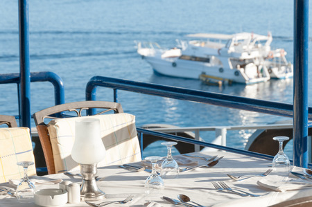 cushioned: Comfortable restaurant seating with a carefully set table and an inspiring view of luxury yachts on a tropical bay.