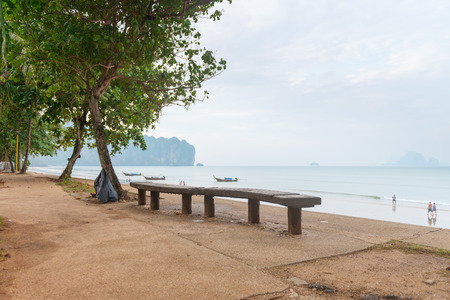 aonang: Outdoor long wooden bench along a walkway under a tree next to the beach with a cloudy sky and boats in the background Stock Photo
