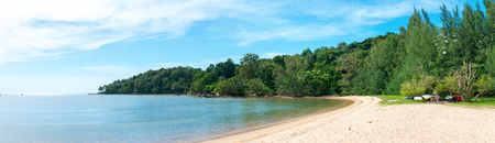 pristine: Panoramic view of a pristine, curving, tree lined tropical beach with wispy cirrus clouds overhead. Stock Photo
