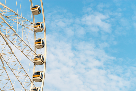 outside machines: Several glass walled gondolas of an enormous Ferris wheel provide dramatic views as they carry passengers up into the sky. Stock Photo