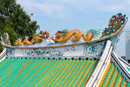 colorfully: Intricately carved and colorfully painted roof sculptures of dragons, mounted atop an ornate, Chinese style temple in Bangkok, Thailand.