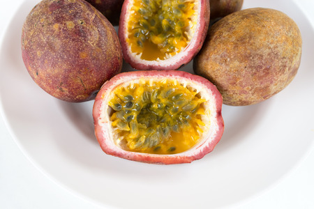insides: Several ripe passion fruit on a white plate, with one sliced open to reveal its sticky insides and many small seeds