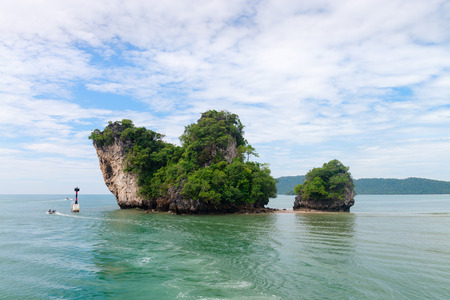 uninhabited: Two small uninhabited green and rock islands near Krabi, Thailand with a buoy, and boats passing by Stock Photo