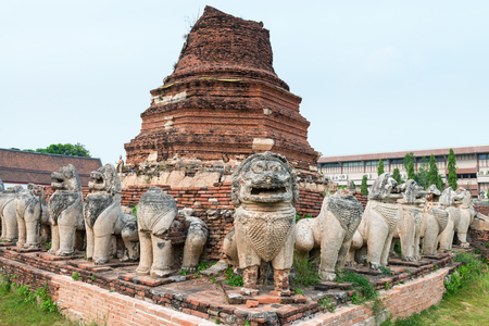 beings: Many, ancient lion sculptures of mythical beings encircle an  stupa in a defensive posture, at Wat Thammikarat in Ayutthaya, Thailand.