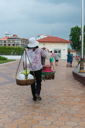 penh: PHNOM PENH, CAMBODIA - 16 DEC 2013: Local vendor carrying street foods on a shoulder mounted rack. Editorial