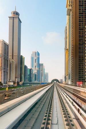 ultra modern: DUBAI, UAE - 16 JULY 2014: Dubais metro rail line, with ultra modern highrise buildings on either side.
