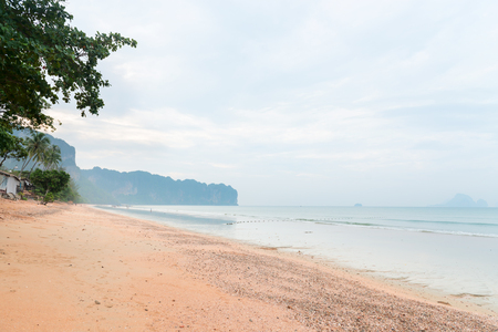 aonang: Deserted beach with trees and a head land in the distance, clean sand outdoors with a hazy sky. Stock Photo