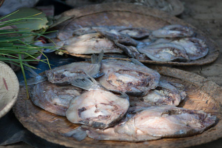 gutted: Gutted and butterflied fresh fish, salted and left to dry in the sun, on woven plates of natural fibers.