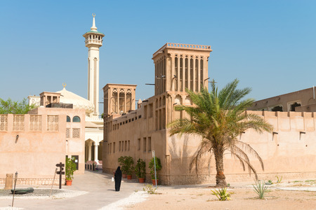 bastakiya: Woman in traditional muslim black dress in old arabic city district with mosque minaret on background