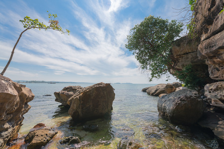 Tropical cove with trees over head and a cloudy sky and sea in the background on a beautiful clear day at Sihanoukville, Cambodia.