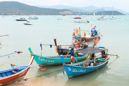 SAMUI, THAILAND - 04 MAR 2013: Traditional thai wooden fishing boats are near the shore with many motor boats on the background Editorial