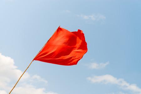 青空を背景に、ビーチに赤い旗。危険性について警告