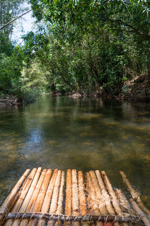 Bamboo rafting in green tropical scenery as a tour for tourist in Thailand Stock Photo