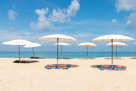 sunshade: White idyllic beach parasol sunshade on sand beach with blue clear sea and a bit cloudy sky on background