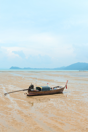 Traditional thai long-tail wooden fishing boat on the deserted sandy sea shore in low-tide time