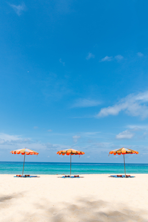 Three empty sunbeds and beach parasol sunshades on sand beach with blue sea and sky on background