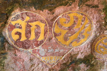 KAO LAK, THAILAND - 24 FEB 2017: Royal cypher or monograms of Thailand king on rock wall in Wat Suwan Khuha (monkey cave temple)