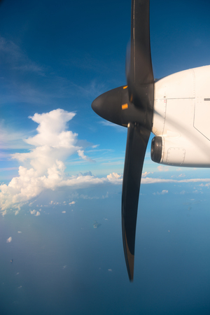 Running turbo aircraft propeller in blue sky and the blue sea with small islands on background
