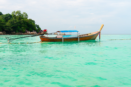 Tourist wooden boat on the clear turquoise sea water with green island on background Stock Photo